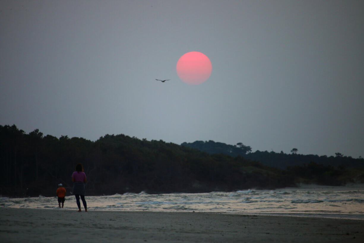 A couple walks along the beach in Cherry Grove, S.C., early Thursday, July 22, 2021. Smoke from wildfires in the western U.S. and Canada is blanketing much of the continent, including thousands of miles away on the East Coast. And experts say the phenomenon is becoming more common as human-caused global warming stokes bigger and more intense blazes.
