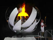 Naomi Osaka stands beside the Olympic flame after lighting it during the opening ceremony in the Olympic Stadium at the 2020 Summer Olympics, Friday, July 23, 2021, in Tokyo, Japan. (AP Photo/David J.