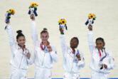 United States' artistic gymnastics women's team members, from left, Sunisa Lee, Grace McCallum, Simone Biles and Jordan Chiles celebrate on the podium after winning the silver medal in the artistic women's team the 2020 Summer Olympics, Tuesday, July 27, 2021, in Tokyo.