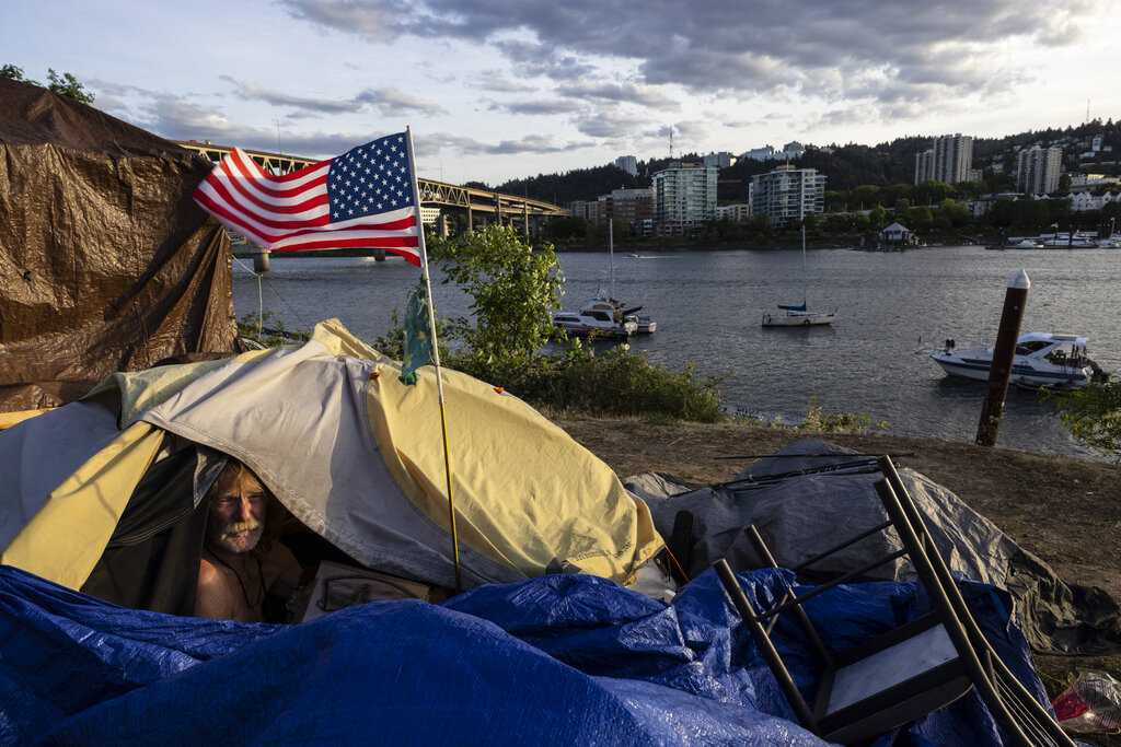 FILE - In this June 5, 2021, file photo, Frank, a homeless man sits in his tent with a river view in Portland, Ore. Portland, Oregon, has banned homeless people from camping in forested parks to both protect them from potential wildfires and prevent them from accidentally starting blazes. The City Council adopted the rule Wednesday, June 28, 2021, amid a summer of drought and record-breaking heat.