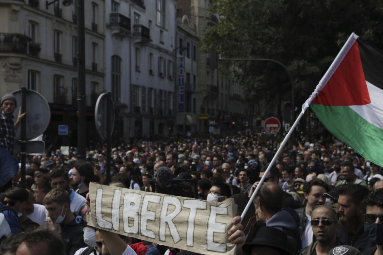 Protestors hold up a banner which reads 'freedom' in French during a demonstration in Paris, France, Saturday, July 31, 2021. Demonstrators gathered in several cities in France on Saturday to protest against the COVID-19 pass, which grants vaccinated individuals greater ease of access to venues.