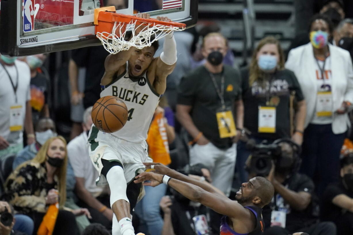 Milwaukee Bucks forward Giannis Antetokounmpo, top, dunks over Phoenix Suns guard Chris Paul during the second half of Game 5 of basketball's NBA Finals, Saturday, July 17, 2021, in Phoenix. (AP Photo/Ross D.