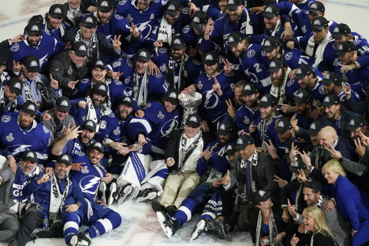 The Tampa Bay Lightning team poses with the Stanley Cup after Game 5 of the NHL hockey Stanley Cup finals against the Montreal Canadiens, Wednesday, July 7, 2021, in Tampa, Fla.