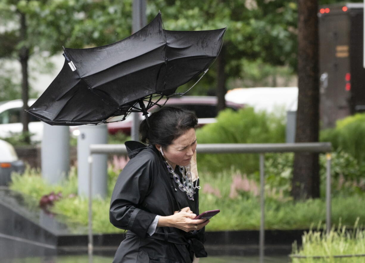A woman's umbrella is flipped inside out as she walks on a rainy and windy New York street, Friday, July 9, 2021. Fast-moving Tropical Storm Elsa hit the New York City region with torrential rains and high winds as it churned up the East Coast.