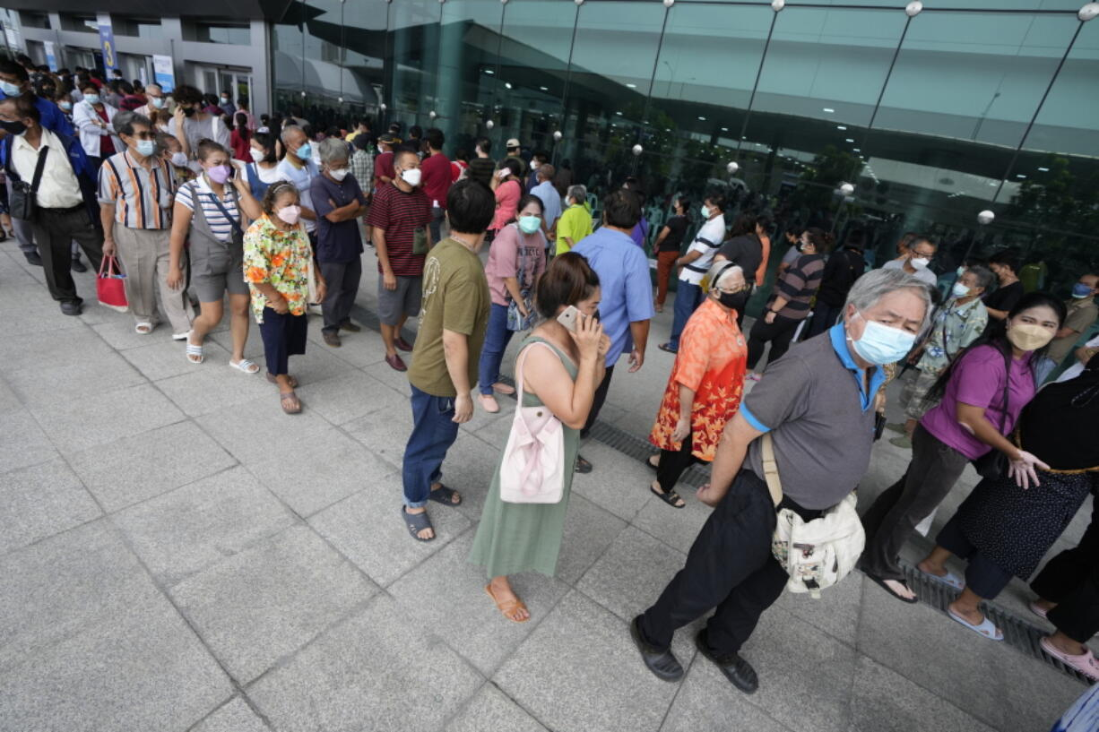 Residents wait on line to receive shots of the AstraZeneca COVID-19 vaccine at the Central Vaccination Center in Bangkok, Thailand, Thursday, July 22, 2021.