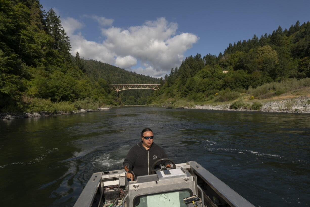 Jamie Holt, lead fisheries technician for the Yurok Tribe, maneuvers a boat near a fish trap in the lower Klamath River on June 8 in Weitchpec, Calif. An historic drought and low water levels are threatening the existence of fish species along the 257-mile-long river.