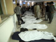 FILE - In this May 8, 2021 file photo, Afghan men try to identify the dead bodies at a hospital after a bomb explosion near a school west of Kabul, Afghanistan. In a report released Monday, July 26, 2021, the United Nations said that more women and children were killed and wounded in Afghanistan in the first half of 2021 than in any year since the UN began keeping count in 2009.