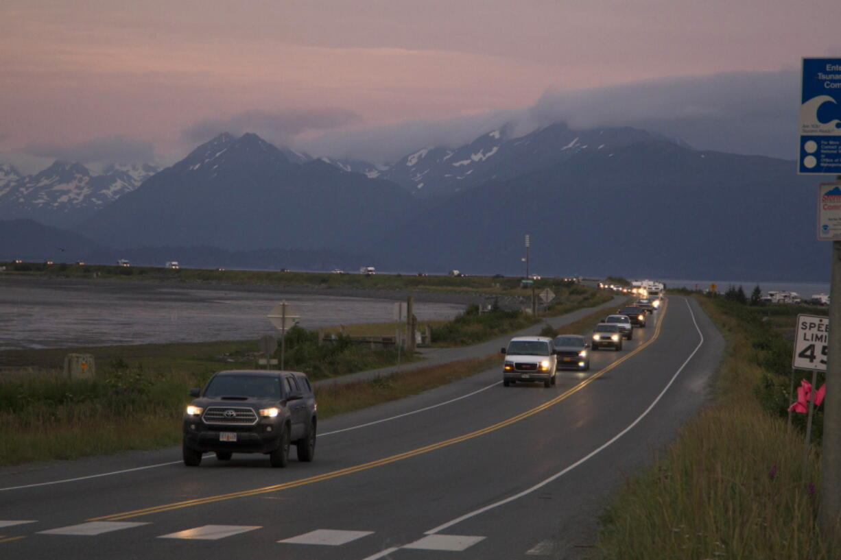 A line of cars evacuates the Homer Spit in Homer, Alaska on July 28, 2021, after a tsunami warning was issued following a magnitude 8.2 earthquake. The tsunami warning for much of Alaska's southern coast was canceled when the biggest wave, of just over a half foot, was recorded in Old Harbor. Alaska.