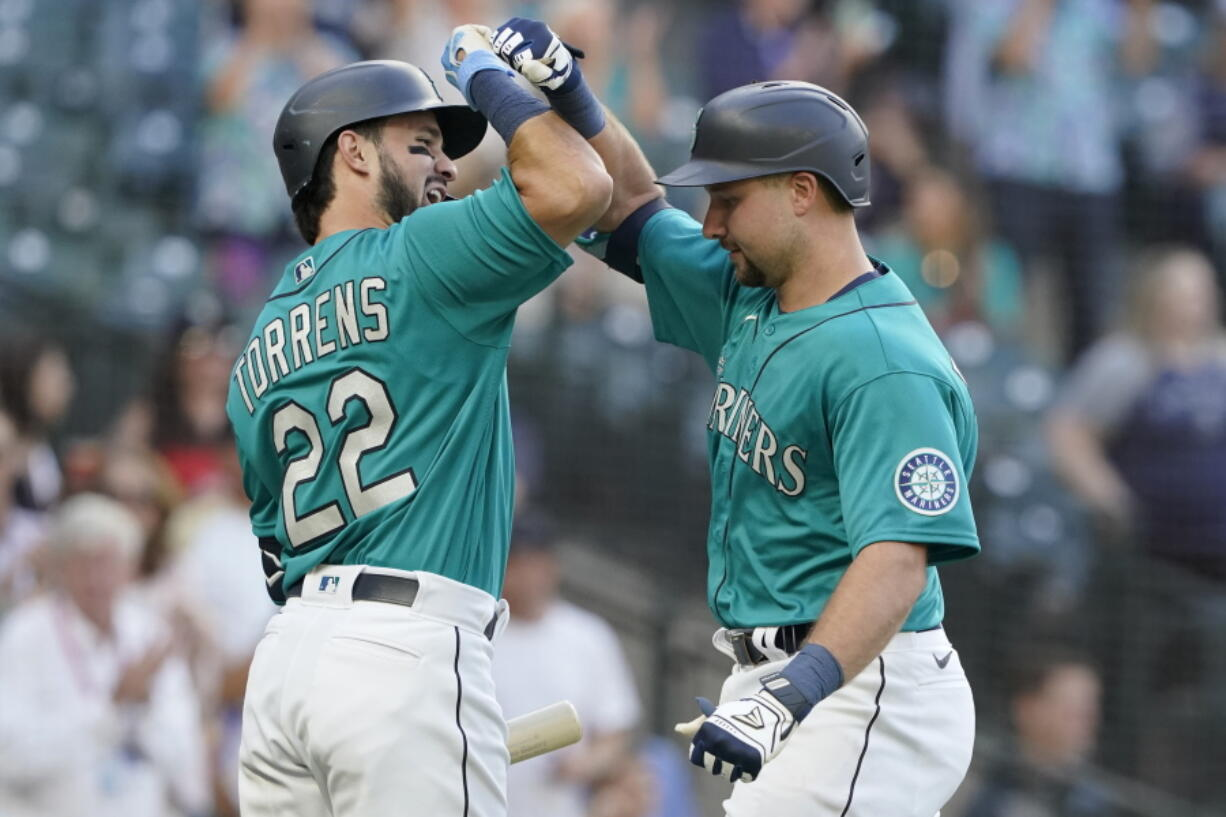 Seattle Mariners' Cal Raleigh, right, is greed by Luis Torrens (22) after Raleigh hit a two-run home run against the Oakland Athletics during the second inning of a baseball game, Friday, July 23, 2021, in Seattle. Torrens hit a solo home run in his ensuing at-bat. (AP Photo/Ted S.
