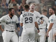 Seattle Mariners' Jarred Kelenic, center, hugs Cal Raleigh (29) after being covered with powder by teammates after Kelenic scored the winning run on a wild pitch during the ninth inning of the team's baseball game against the Oakland Athletics, Saturday, July 24, 2021, in Seattle. The Mariners won 5-4. (AP Photo/Ted S.