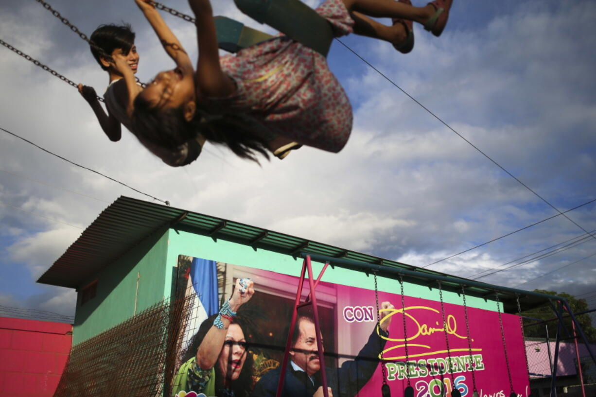 FILE - In this Nov. 4, 2016 file photo, children swing in a park next to an election billboard for President Daniel Ortega and his running mate, his wife, Rosario Murillo in Managua, Nicaragua. In June 2021, amid a weekslong clampdown to obliterate nearly every hint of opposition, Ortega ordered the arrest of Hugo Torres, a revered guerrilla in the fight against right-wing dictator Anastasio Somoza. In 1974, Torres had taken a group of top officials hostage, then traded them for the release of imprisoned comrades, among them, Daniel Ortega.