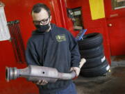 FILE - In this Feb. 5, 2021 file photo, Ari Thielman, manager at GT Tire & Service Center, holds a catalytic converter from a Ford F-150 that the 155 Colony St. business replaced for a customer in Meriden, Conn.