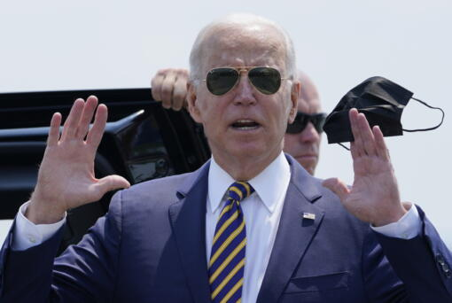President Joe Biden holds a mask as he responds to a question as he arrives at Lehigh Valley International Airport in Allentown, Pa., Wednesday, July 28, 2021. Biden is in the area to visit the Lehigh Valley operations facility for Mack Trucks and advocate for government investments and clean energy as ways to strengthen U.S. manufacturing.