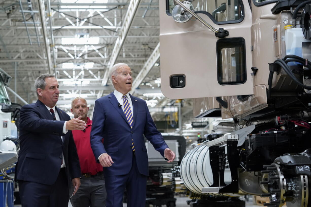 President Joe Biden reacts as Mack Trucks President Martin Weissburg, left, speaks during a tour of the Lehigh Valley operations facility for Mack Trucks in Macungie, Pa., Wednesday, July 28, 2021. UAW Local 677 Shop Chairman Kevin Fronheiser is at center.