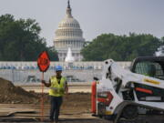 Workers repair a park near the Capitol in Washington, Wednesday, July 21, 2021, as senators struggle to reach a compromise over how to pay for nearly $1 trillion in public works spending, a key part of President Joe Biden's agenda. (AP Photo/J.