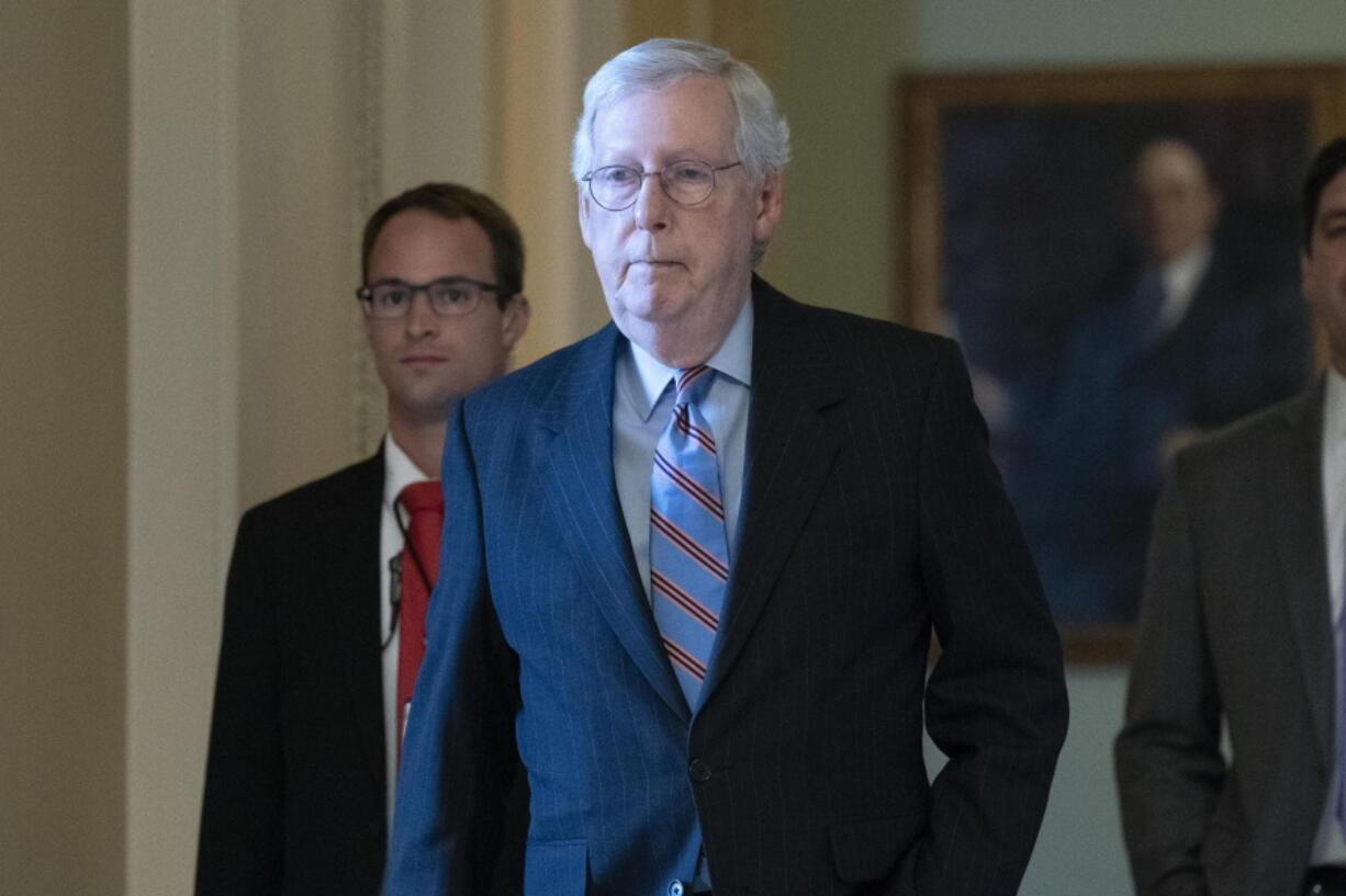 Senate Minority Leader Mitch McConnell, R-Ky., center, walks to his office at the Capitol ahead of a test vote schedule by Democratic Leader Chuck Schumer of New York on the bipartisan infrastructure deal senators brokered with President Joe Biden, in Washington, Wednesday, July 21, 2021. Republicans prepared to block the vote by mounting a filibuster over what they see as a rushed and misguided process.