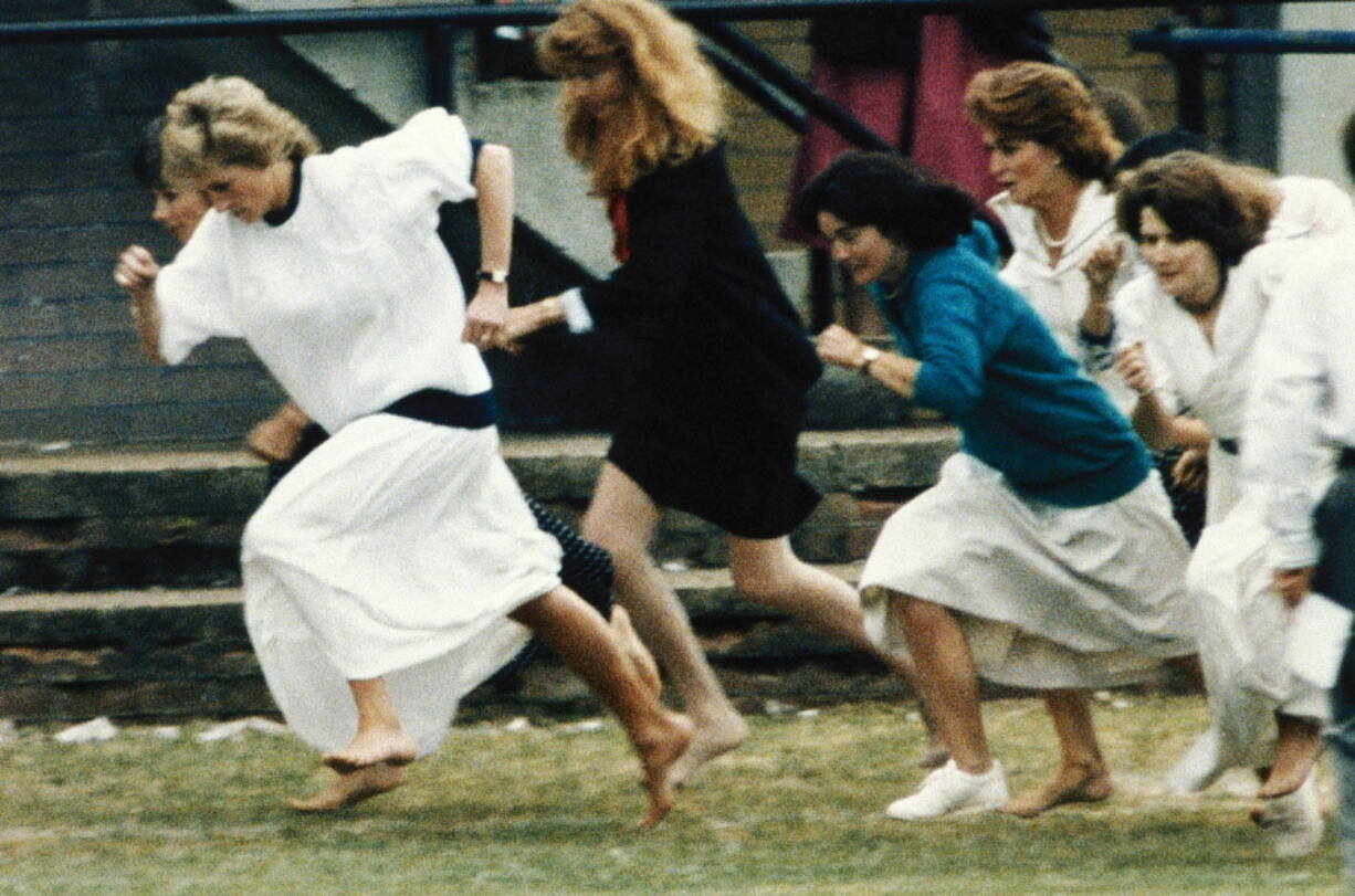 """FILE - In this file photo dated Tuesday, June 28, 1989, Britain's Princess Diana wearing a white dress, races ahead during the mother's race, held during a sports day for Wetherby school, where her son Prince William is a pupil. T For someone who began her life in the spotlight as """"Shy Di,"""" Princess Diana became an unlikely, revolutionary during her years in the House of Windsor. She helped modernize the monarchy by making it more personal, changing the way the royal family related to people. By interacting more intimately with the public -- kneeling to the level of children, sitting on edge of a patient's hospital bed, writing personal notes to her fans -- she set an example that has been followed by other royals as the monarchy worked to become more human and remain relevant in the 21st century."""
