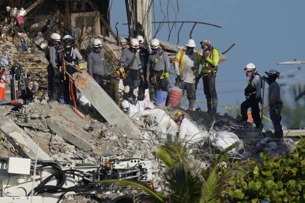 A team works to extricate remains as search and rescue personnel look on, atop the rubble at the Champlain Towers South condo building where scores of people remain missing more than a week after it partially collapsed, Friday, July 2, 2021, in Surfside, Fla.