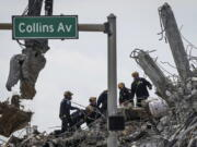Search and rescue operations resumed as members of the Pennsylvania Search and Rescue team combed through the debris of the Champlain Tower South complex, Monday, July 5, 2021, in Surfside, Fla.