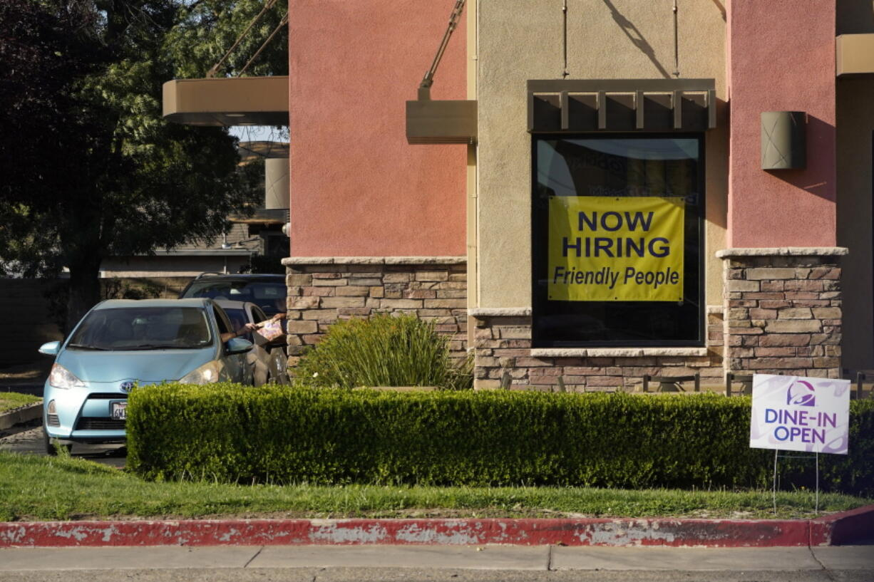 A hiring sign hangs in the window of a Taco Bell in Sacramento, Calif., Thursday, July 15, 2021. Hiring in California slowed down in June as the unemployment rate held steady at 7.7% according to new numbers released on Friday, July 16, 2021 by the Employment Development Department. California gained 73,000 jobs in June, ending the state's streak of four consecutive months of adding 100,000 jobs or more.