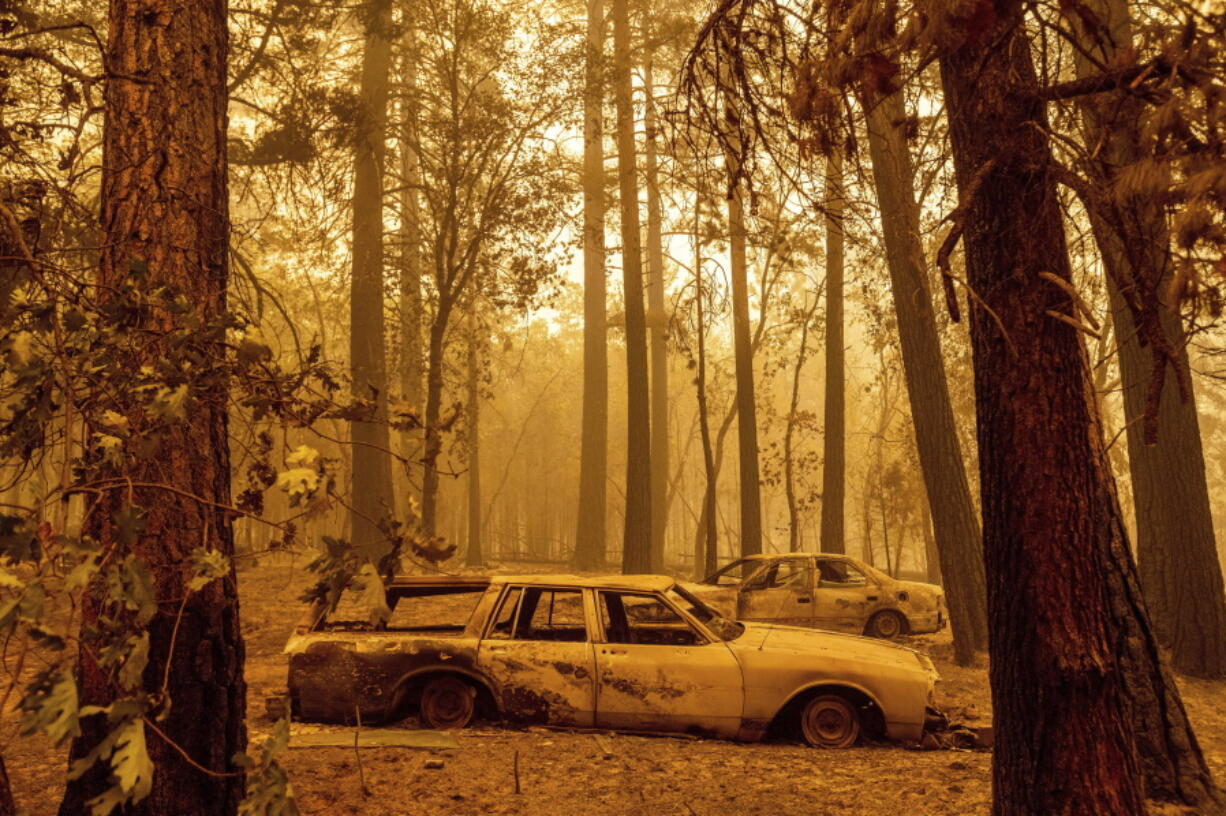 Following the Dixie Fire, scorched cars are seen in a clearing in the Indian Falls community of Plumas County, Calif., on Sunday, July 25, 2021.