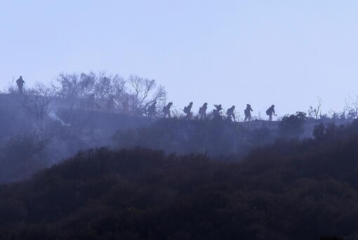 A hotshot hand crew walks in line during a wildfire in Topanga, west of Los Angeles, Monday, July 19, 2021. A brush fire scorched about 15 acres in Topanga today, initially threatening some structures before fire crews got the upper hand on the blaze, but one firefighter suffered an unspecified minor injury. (AP Photo/Ringo H.W.