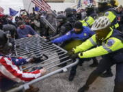 FILE - In this Jan. 6, 2021, file photo violent insurrectionists loyal to President Donald Trump hold on to a police barrier at the Capitol in Washington. Months after Donald Trump's supporters besieged the Capitol, the ex-president and his supporters are revising their account of that day.