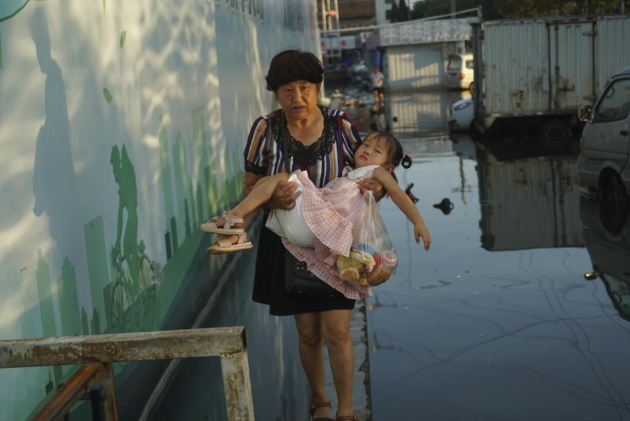A woman carries a child in her arms as she walks on a curb above floodwaters in Xinxiang in central China's Henan Province, Monday, July 26, 2021. Record rain in Xinxiang last week left the produce and seafood market soaked in water. Dozens of people died in the floods that immersed large swaths of central China's Henan province in water.