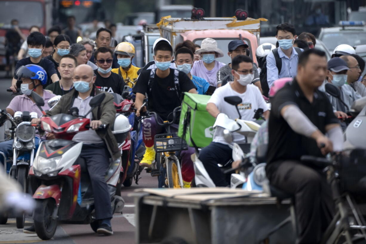 FILE - In this file photo dated Friday, July 2, 2021, people riding bicycles and scooters wait to cross an intersection during rush hour in Beijing.  China has failed to submit fresh targets for cutting their greenhouse gas emissions, UN climate change officials said Saturday July 31, 2021, among some dozens that failed provide an update on their plans by the July 31 deadline.