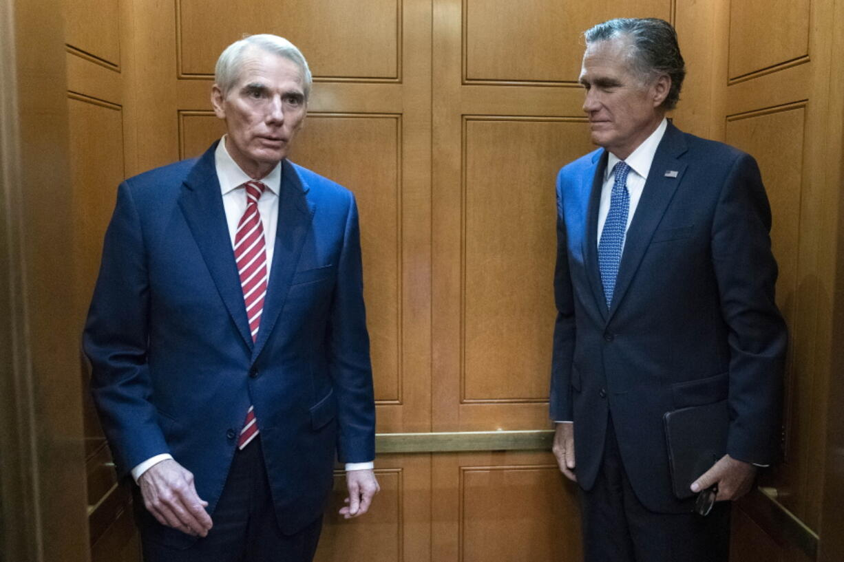 Sen. Rob Portman, R-Ohio, left, accompanied by Sen. Mitt Romney, R-Utah, leave in the elevator after a closed door talks about infrastructure on Capitol Hill in Washington Thursday, July 15, 2021.