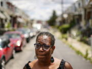 In this July 9, 2021 photo, Michelle Bolling poses for a photograph outside of her home in Philadelphia. Bolling's son is one of the increasing numbers of nonfatal gun violence victims. Homicide rates in many American cities have continued to rise although not as precipitously as the double-digit jumps seen in 2020 and still below the violence of the mid-90s.