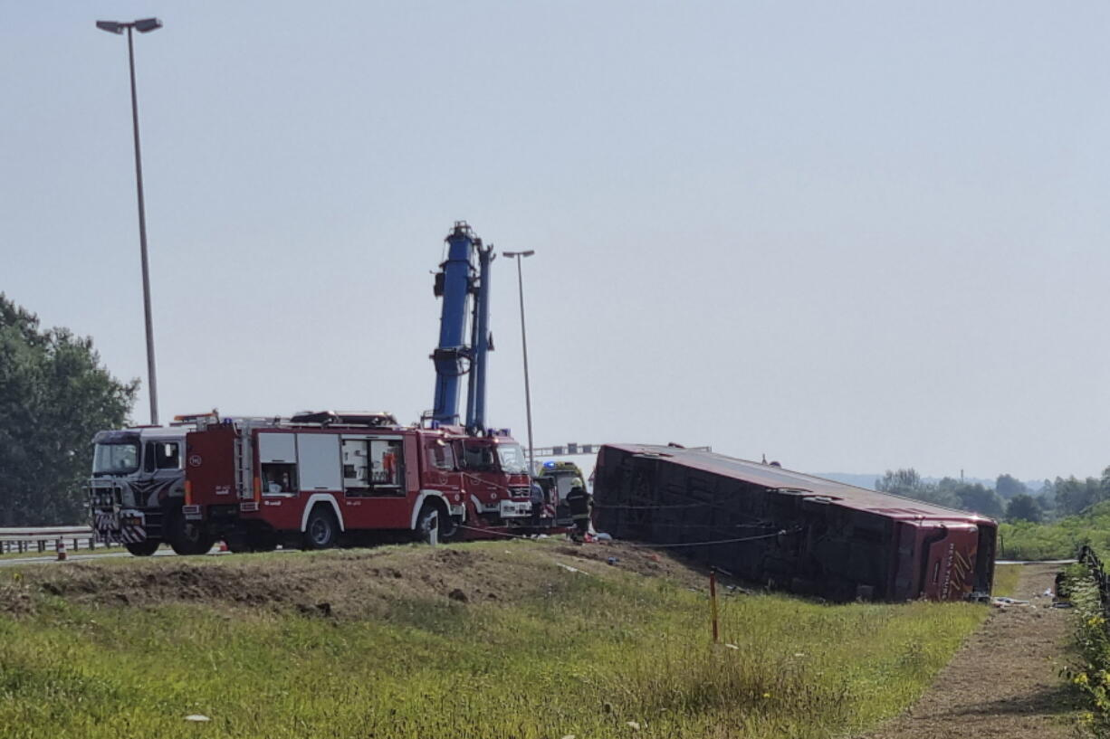 Emergency crews work at the site of a bus accident near Slavonski Brod, Croatia, Sunday, July 25, 2021. A bus swerved off a highway and crashed in Croatia early Sunday, killing 10 people and injuring at least 30 others, police said.