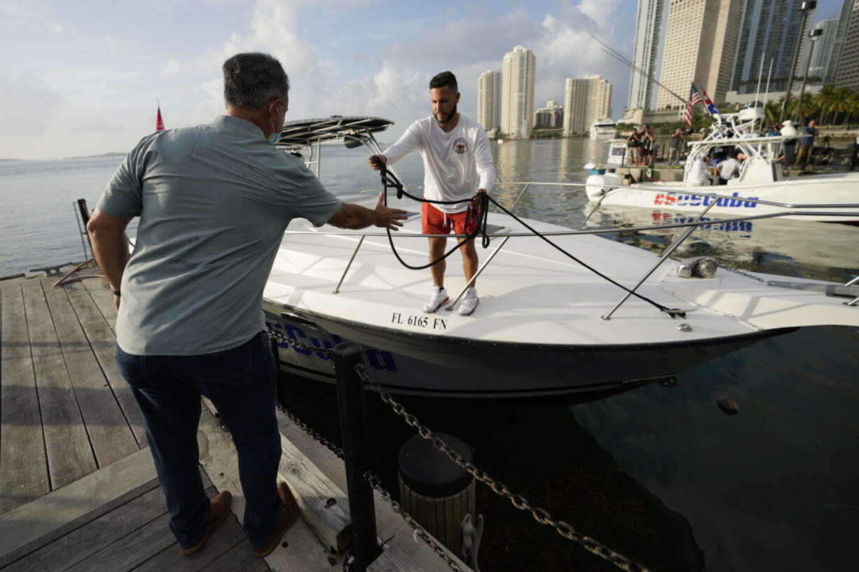 Ramon Saul Sanchez, left, leader of the nonprofit group Movimiento Democracia that launched several flotillas in the past, helps boater Julio Gonzalez tie up his boat, Friday, July 23, 2021, in downtown Miami. A small group of Cuban Americans launched motorboats from Miami to their homeland to show support for people experiencing hardships on the island. Five boats left the Bayside marina just before 8 a.m. Friday. They plan to refuel in Key West before heading into the Florida Straits.
