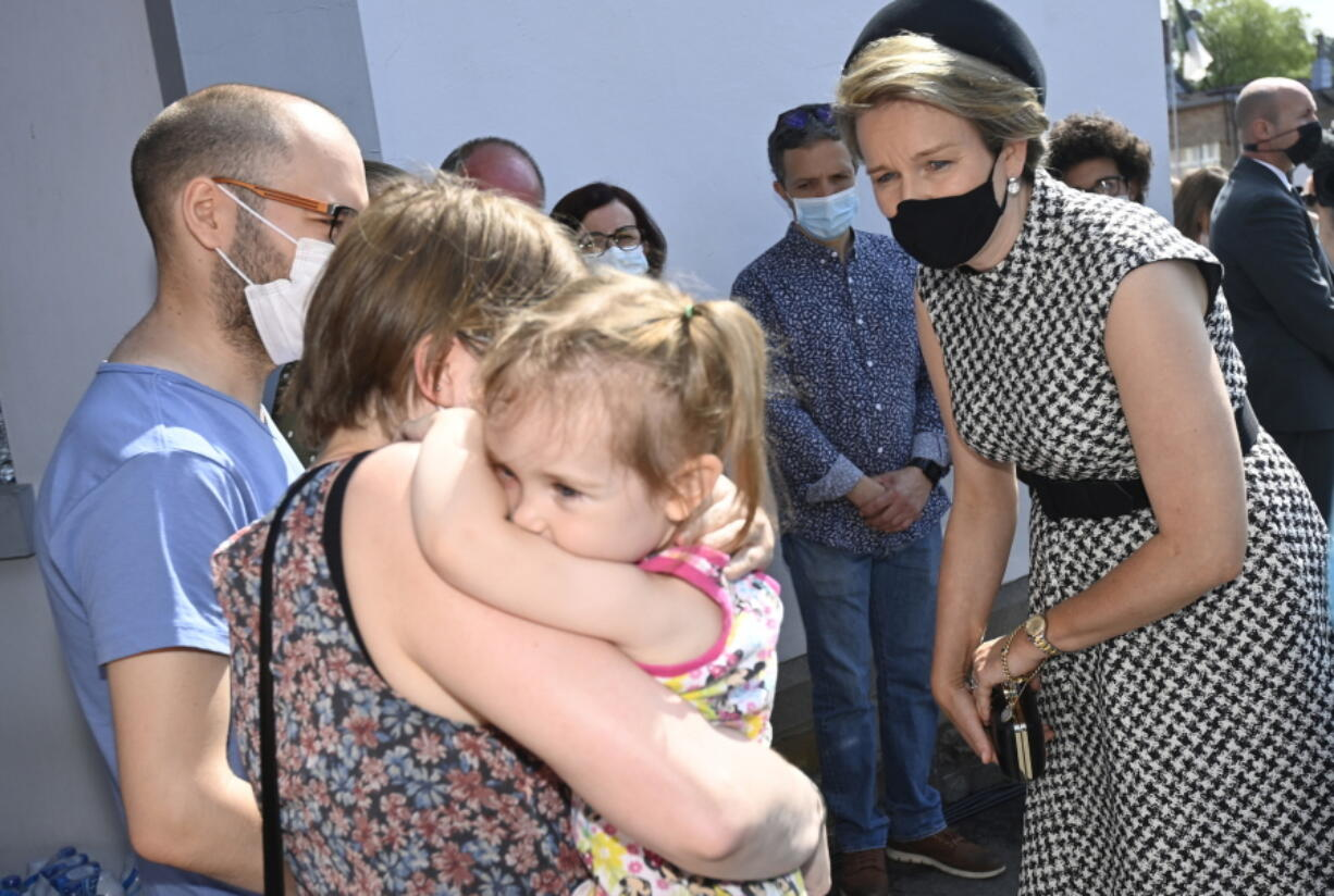 Belgium's Queen Mathilde, right, speaks with residents affected by the floods, prior to participating in a ceremony of one minute of silence to pay respect to victims of the recent floods in Belgium, in Verviers, Belgium, Tuesday, July 20, 2021. Belgium is holding a day of mourning on Tuesday to show respect to the victims of the devastating flooding last week, when massive rains turned streets in eastern Europe into deadly torrents of water, mud and flotsam.