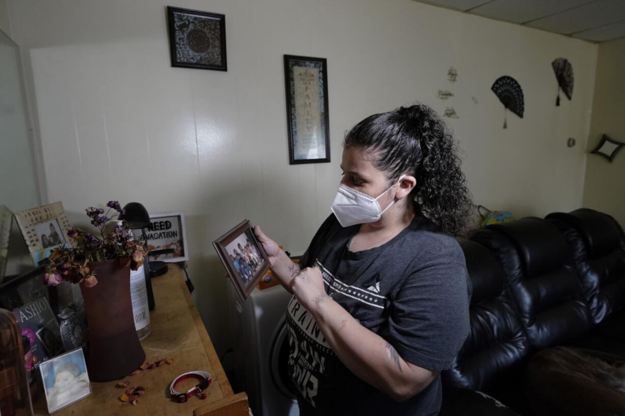 Roxanne Schaefer holds a photograph in the living room of her apartment, in West Warwick, R.I., Tuesday, July 27, 2021. Schaefer, who is months behind on rent, is bracing for the end to a CDC federal moratorium Saturday, July 31, 2021, a move that could result in millions of people being evicted just as the highly contagious delta variant of the coronavirus is rapidly spreading.