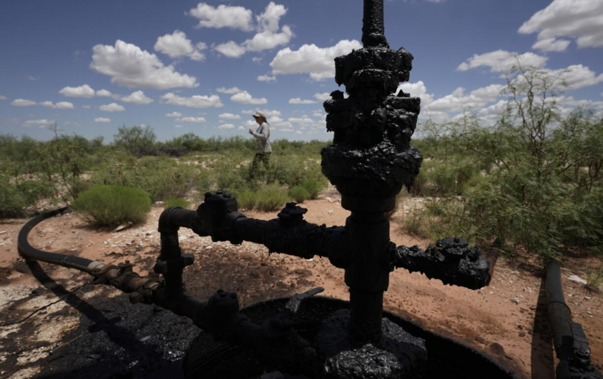 Ashley Williams Watt walks near a wellhead and flowline at her ranch, Friday, July 9, 2021, near Crane, Texas. The wells on Watt's property seem to be unplugging themselves. Some are leaking dangerous chemicals into the ground, which are seeping into her cattle's drinking water. And she doesn't know how long it's been going on.