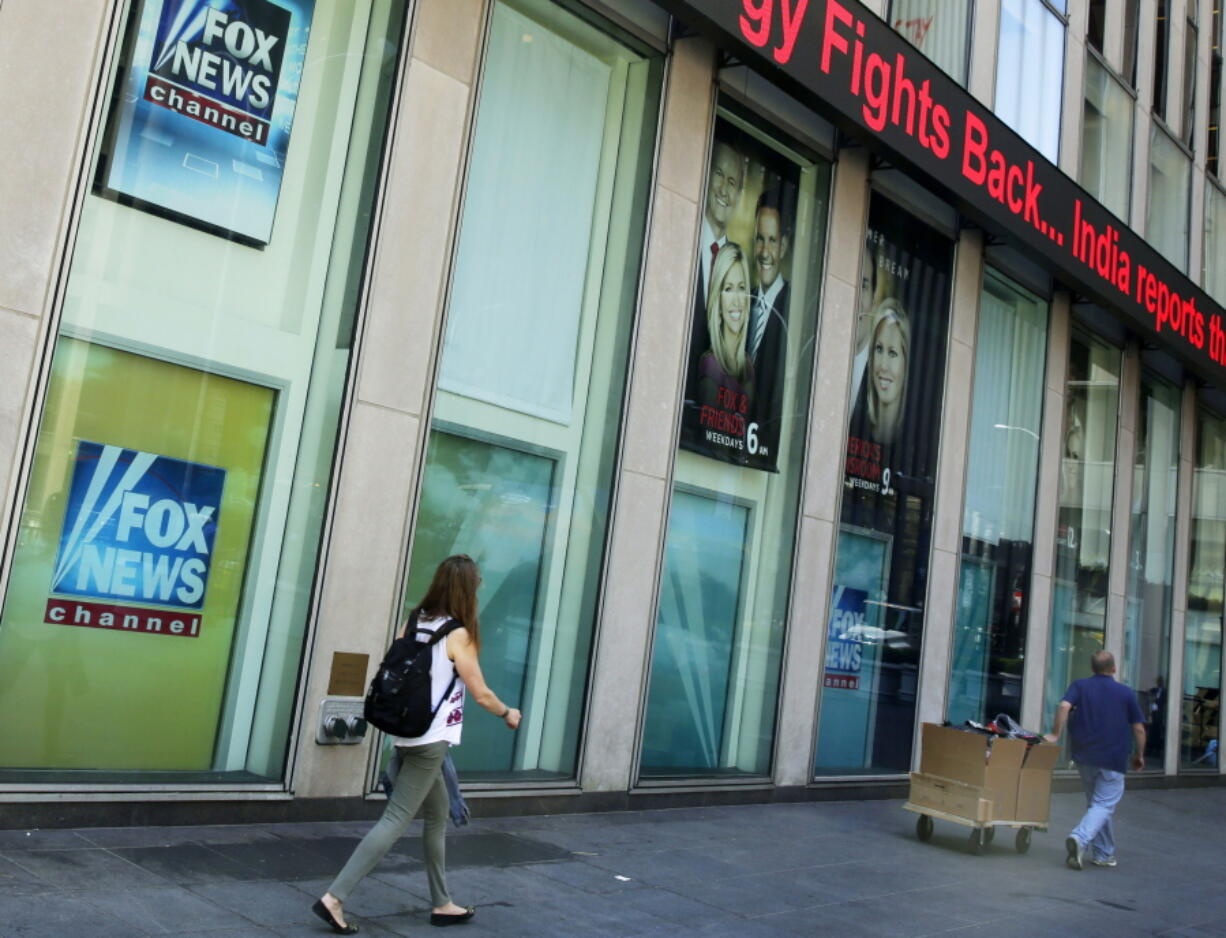 FILE- People pass the News Corporation headquarters building and Fox News studios in New York on Aug. 1, 2017.  New York City's human rights commission has fined Fox News $1 million for violation of laws protecting against sexual harassment and job retaliation. It's the largest such penalty in the commission's history.