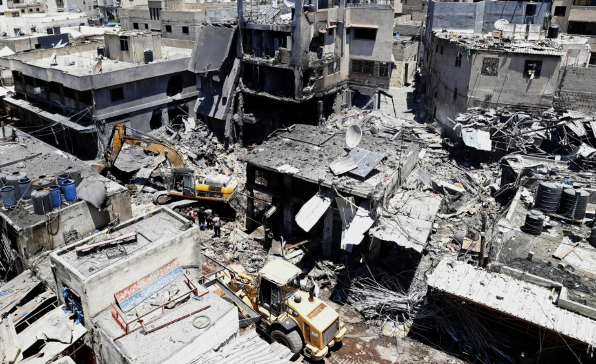 Palestinian rescuers and security personnel work at the scene of an explosion in the Al-Zawiya market area of Gaza City, Gaza, Thursday, July 22, 2021. At least one person was killed and some 10 injured Thursday when the explosion tore through a house in a popular market, the interior ministry said.