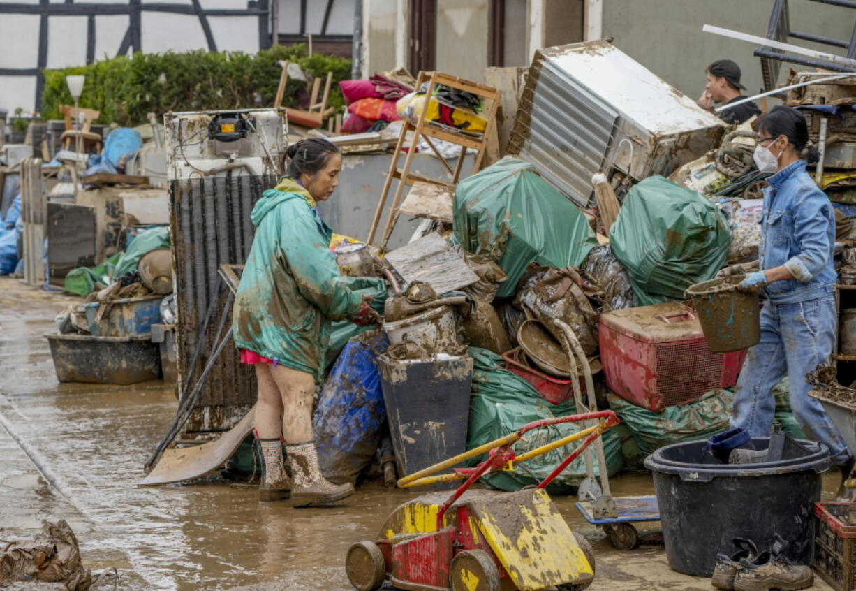 People clean their homes from mud and debris in Bad Neuenahr-Ahrweiler, Germany, Saturday, July 17, 2021. Due to strong rainfall, the Ahr river went over its banks and flooded big parts of the town.