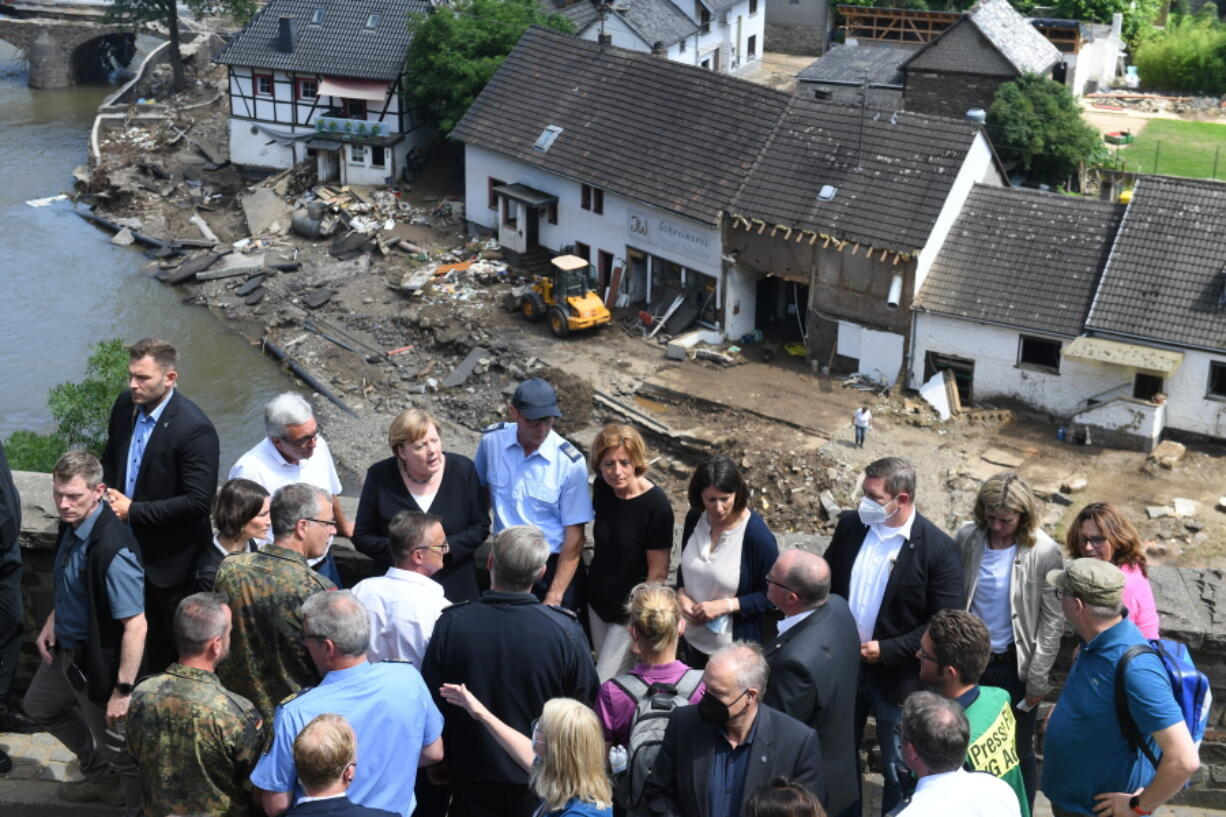 German Chancellor Angela Merkel, rear third left, and the Governor of the German state of Rhineland-Palatinate, Malu Dreyer, rear fifth left, are seen on a bridge in Schuld, western Germany, Sunday, July 18, 2021 during their visit in the flood-ravaged areas to survey the damage and meet survivors. After days of extreme downpours causing devastating floods in Germany and other parts of western Europe the death toll has risen.