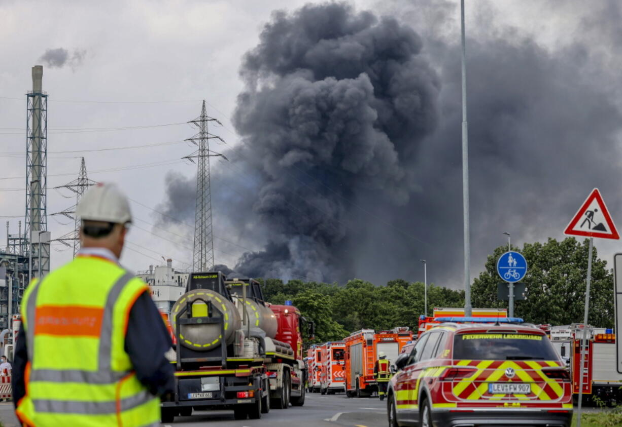 Emergency vehicles of the fire brigade, rescue services and police stand not far from an access road to the Chempark over which a dark cloud of smoke is rising in Leverkusen, Germany, Tuesday, July 27, 2021.. After an explosion, fire brigade, rescue services and police are currently in large-scale operation, the police explained.