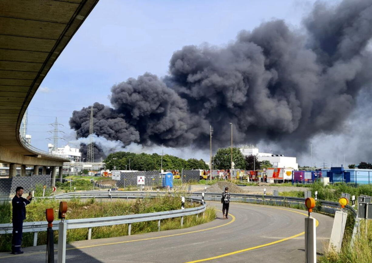 A dark cloud of smoke rises above the chemical park in Leverkusen, Germany, Tuesday, July 27, 2021. Firefighters from the site fire department are on duty.