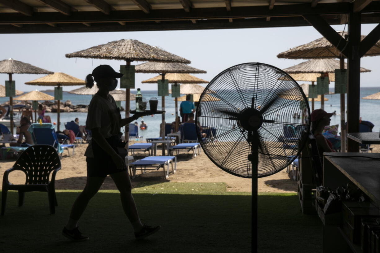 A waitress serves refreshments at a beach bar of Lagonissi village, a few miles southwest of Athens, on Thursday, July 29, 2021. One of the most severe heat waves recorded since 1980s scorched southeast Europe on Thursday, sending residents flocking to the coast, public fountains and air-conditioned locations to find some relief, with temperatures rose above 40 C (104 F) in parts of Greece and across much of the region.