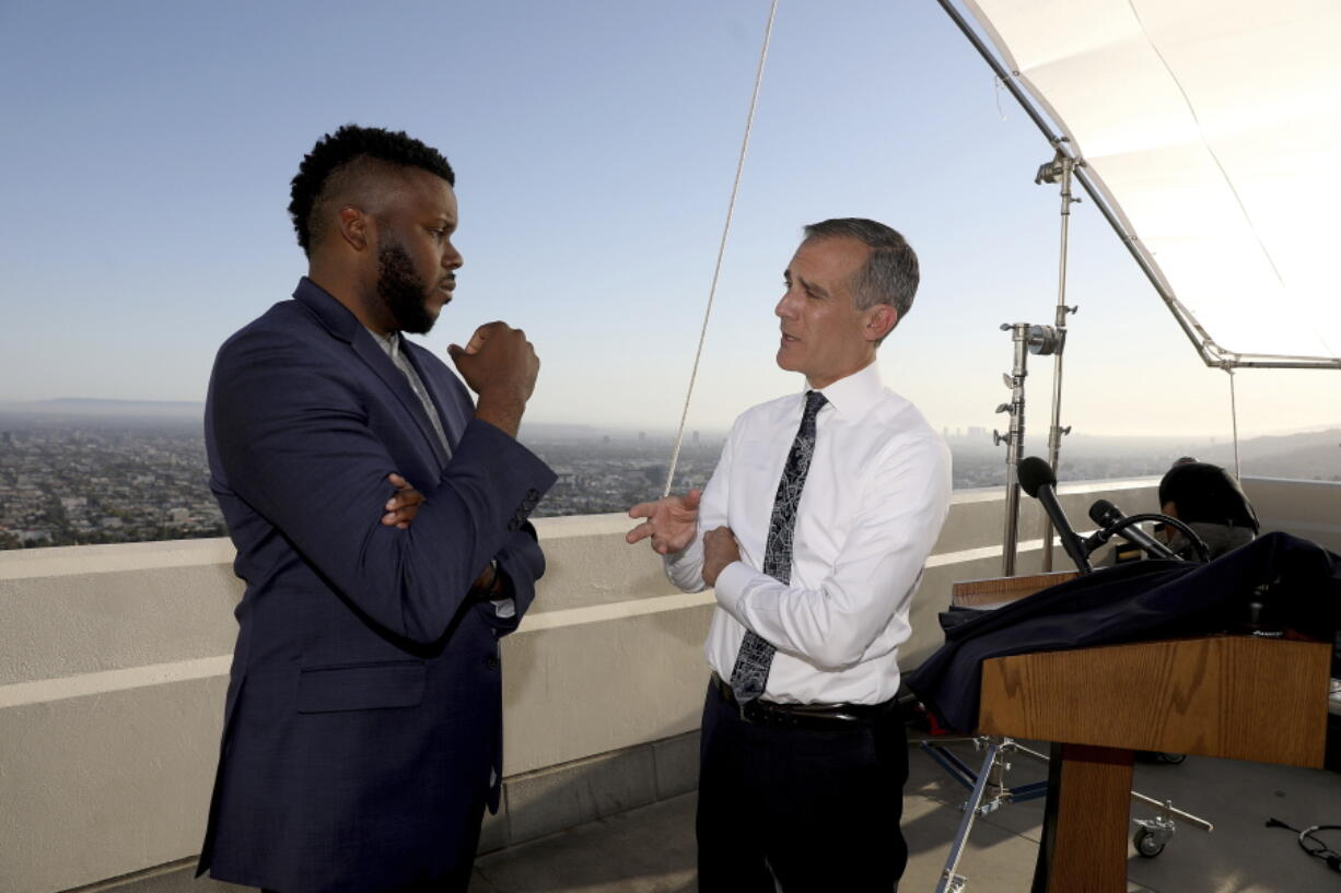 FILE - In this April 19, 2021 file photo, Los Angeles Mayor Eric Garcetti, right, talks with Michael Tubbs, founder of Mayors for a Guaranteed Income, after holding his annual State of the City address from the Griffith Observatory, in Los Angeles. In experiments across the country, dozens of cities and counties, some using money from the $1.9 trillion COVID relief package approved in March, and the state of California are giving some low-income residents a guaranteed income of $500 to $1,000 each month to do with as they please, and tracking what happens.