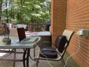 Designer Melissa Rayworth says a lumbar pillow and seat cushion added to an outdoor dining chair help create a more ergonomic outdoor workspace. Millions of people found themselves working from home during the past year.