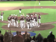 The Ridgefield Raptors await Kody Darcy at home plate after his three-run homer gave Ridgefield a 8-5 win over the Bellingham Bells in 10 innings on Thursday in Ridgefield.