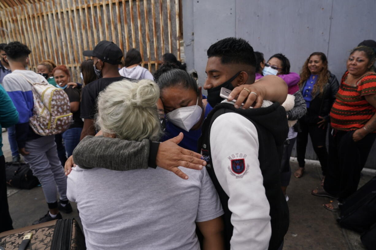 FILE - In this July 5, 2021, file photo, Alex Cortillo, right, of Honduras gets a hug from Erika Valladares Ponce, of Honduras, center, and others, as he waits to cross into the United States to begin the asylum process in Tijuana, Mexico. Two nongovernmental organizations said Friday, July 30, 2021, that they are ending cooperation with the Biden Administration to identify the most vulnerable migrants waiting in Mexico to be admitted to the United States to seek asylum.