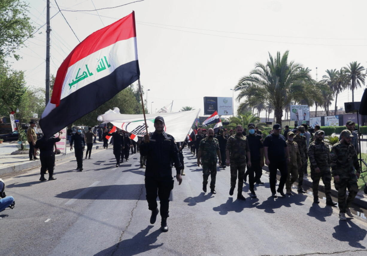 Iran-backed militia fighters march in central Baghdad, Iraq, Tuesday, June 29, 2021. Iraqi Shiite militias are showing a degree of defiance of their patron Iran by escalating rocket and drone attacks on the U.S. presence in the country, militia and Shiite political leaders say. Iran has been pushing the factions to keep calm in Iraq while it holds nuclear negotiations with the United States.