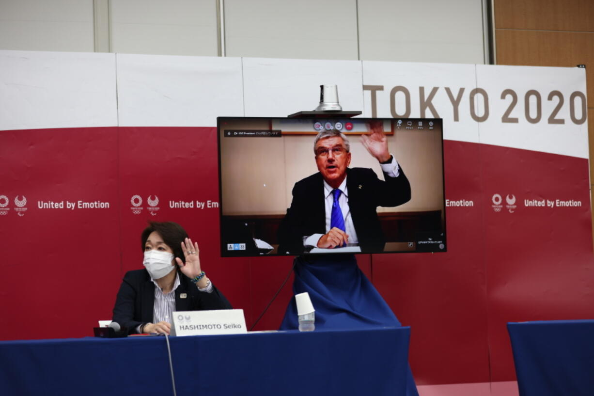 International Olympic Committee (IOC) president Thomas Bach (on-screen) and Tokyo 2020 president Seiko Hashimoto, left, wave at the beginning of the five-party meeting in Tokyo, Thursday, July 8, 2021.