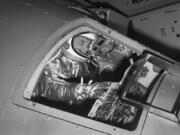 FILE - In this Jan. 11, 1961 file photo, then Marine Lt. Col. John Glenn reaches for controls inside a Mercury capsule procedures trainer as he shows how the first U.S. astronaut will ride through space during a demonstration at the National Aeronautics and Space Administration Research Center in Langley Field, Va. Glenn's birthplace and childhood hometown in Ohio are celebrating what would have been the history-making astronaut and U.S. senator's 100th birthday with a three-day festival from July 16 through July 18, 2021.